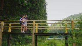 Een paar toeristen lopen voorzichtig over een brug over een bergrivier stock footage