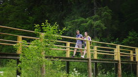 Een paar toeristen lopen voorzichtig over een brug over een bergrivier stock videobeelden