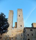 Een paar torens van San Gimignano in Italië tegen diepe blauwe die hemel, door bleke het plaatsen zon worden aangestoken stock afbeelding