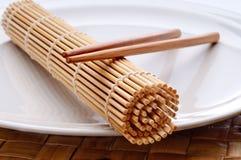 Een paar van eetstokjes en een sushi rollende mat stock foto's