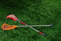Een paar van lacrosse plakt het leggen op een gebied stock fotografie