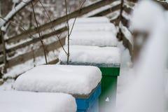 Een paar van sneeuw behandelde bijenbijenkorven Bijenstal in wintertijd Bijenkorven met sneeuw in wintertijd worden behandeld die stock foto