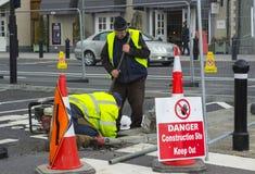 Een paar werklieden voeren essentiële onderhoudsreparaties bij het Dorp van Ierland ` s Kildare kleinhandels het winkelen afzet i stock afbeelding