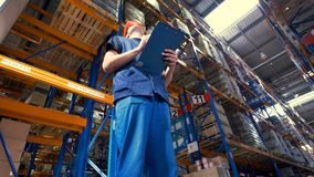 Een pakhuisarbeider dichtbij grote rekken met goederen 4K stock video