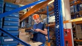 Een pakhuisinspecteur bestudeert goederenbinnenkant opende dozen stock videobeelden