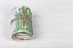 Een pakje van euro rekeningen rolde en bond met een kabel stock foto's