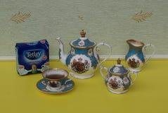 Een pakket van de theezakjes van originele Engelse Tetley daarna een Engels theekopje met schotel, theepot, suikerkom en roomkrui royalty-vrije stock afbeelding