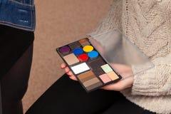 Een palet van schaduwen met verschillende kleuren van het product in de handen van een model in een schoonheidsstudio, waarmee de stock foto's