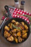 Een pan van gekruide aardappelen in de schil Stock Afbeeldingen