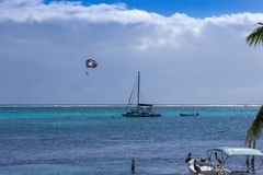 Een parasail drijft weg over de blauwe en azuurblauwe wateren van de Caraïbische Zee van de kust van Belize stock foto's