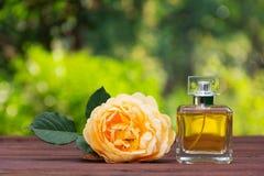 Een parfumfles en geurige geel namen toe Natuurlijk parfum in een vierkante fles op een groene vage achtergrond Stock Foto