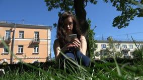 In een park op groen gras, werkt een onderneemster met een nieuwe generatiesmartphone stock footage