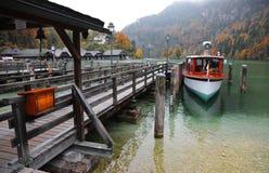 Een parkeren van de sightseeingsboot door de houten pijler bij mooie oever van het meer in een nevelige mistige ochtend op Meer K Stock Foto