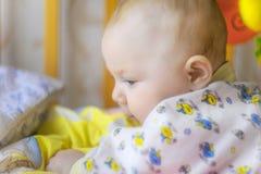 Een pasgeboren baby ligt in een voederbak en speelt met speelgoed, close-up stock foto