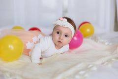 Een pasgeboren meisje ligt in een wit verband en kleedt zich op een bed met gekleurde ballen Het kind zelf houdt zijn hoofd en royalty-vrije stock foto