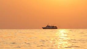 Een passagiersschip vaart het overzees op de horizon tijdens zonsondergang stock footage