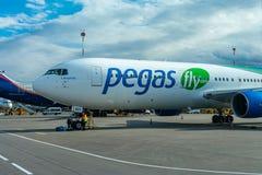 Een passagiersvliegtuig bevindt zich bij de luchthaven in een parkeerplaats die op vertrek, het proces wachten om voorbereidingen royalty-vrije stock afbeelding