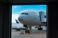 Een passagiersvliegtuig bevindt zich bij de luchthaven in een parkeerplaats die op vertrek, het proces wachten om voorbereidingen royalty-vrije stock foto
