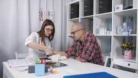 Een patiënt met een verwonde pols in de spreekkamer De arts onderzoekt de pols van de patiënt de arts x onderzoekt stock videobeelden