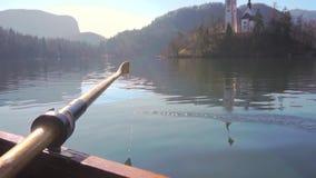 Een peddel in het water op een zonnige dag die - de boot met eiland roeien tapte het meer in het Afgetapte meer af als achtergron stock video