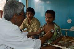 Een pediater controleert een kleine jongen met stethoscoop stock foto