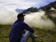 Een peinzende, eenzame mens zit op de grond in een berg royalty-vrije stock foto
