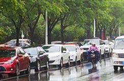 Een personenvervoer een elektrische fiets in de regen Stock Afbeeldingen