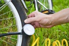 Een persoon blaast een fietswiel met behulp van samengeperste lucht en een drukmaat op Wiel en hand die op de achtergrond wordt g stock fotografie