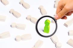 Een persoon is in de schijnwerper Een groen houten cijfer van een mens royalty-vrije stock afbeeldingen