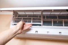 Een persoon die de filters uit de airconditioner verwijdert Stock Afbeeldingen
