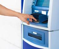 Een persoon die een speldaantal ingaan bij een blauwe ATM-machine Stock Foto