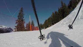Een persoon die onderaan een berghelling ski?en stock video