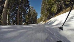 Een persoon die onderaan een berghelling ski?en stock footage