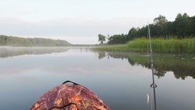 Een persoon die op de opblaasbare boot op de rivier vissen De mensen in een opblaasbare kajak rusten in de de zomerdag op de rivi stock video