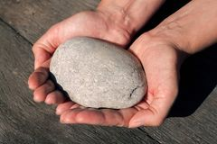 Een persoon die een steen in haar dicht tegenhouden handen royalty-vrije stock foto's