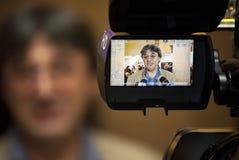 Een persoon door een TV-camera wordt gezien die Stock Afbeelding