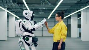 Een persoon en cyborg wat betreft handen, die zich dichtbij elkaar in een ruimte bevinden stock videobeelden