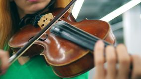 Een persoon gebruikt strijkstok om houten viool te spelen stock video