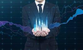 Een persoon houdt een hologram van wolkenkrabbers als symbool van financieel succes Stock Afbeelding