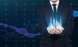 Een persoon houdt een hologram van wolkenkrabbers als symbool van financieel succes Stock Fotografie