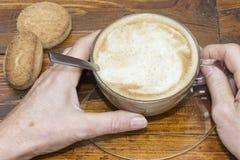 Een persoon houdt een kop van koffie met zijn handen Stock Afbeeldingen