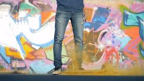Een persoon laat vallen een skateboard met geel poeder, langzame motie stock video