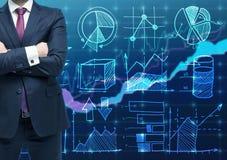 Een persoon met gekruiste handen en in formeel kostuum als handelaar of analistengrafiek van Financial op de achtergrond Het conc royalty-vrije stock afbeeldingen
