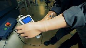 Een persoon met kunstmatige handen werkt met een console, draaiend een handvat 4K