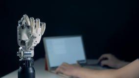 Een persoon met laptop leidt een bewegend mechanisch wapen stock footage
