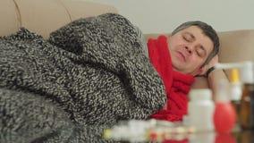 Een persoon met tekens van een koude met een deken wordt behandeld ligt in een flat op de laag en blaast zijn neus in een documen stock videobeelden