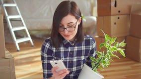 Een persoon met een telefoon en een ingemaakte installatie in de achtergronddozen voor de beweging stock videobeelden