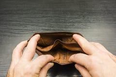 Een persoon onderzoekt een lege portefeuille royalty-vrije stock afbeelding