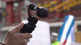Een persoon schiet video op een draagbaar three-axis stabilisatiesysteem stock videobeelden