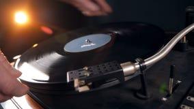 Een persoon verwijdert een vinylverslag uit de speler stock video